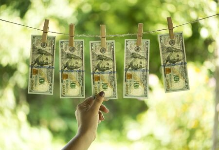 Money laundering concept. One hundred dollar bills are hanging on a rope. Pure money.