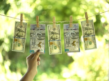 Money laundering concept. One hundred dollar bills and Kazakhstan tenge are hanging on a rope. Pure money.