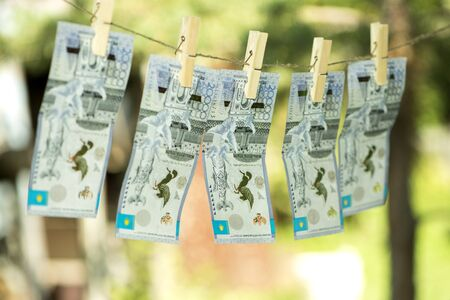 Money laundering concept. Kazakhstan tenge hanging on a rope. Pure money.