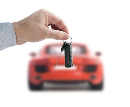 Man hand holding a remote control key in the red sports car on a white background