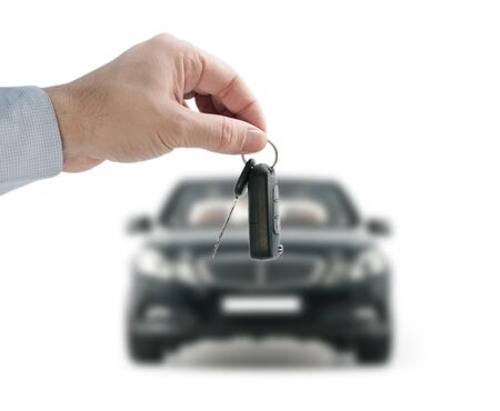 Man hand holding a remote control key in the black car on a white background Stockfoto