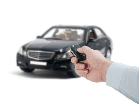 Man hand holding a remote control key near the new black car on a white background Stockfoto