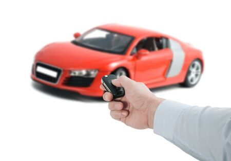 Man hand holding a remote control key near a red sports car on a white background