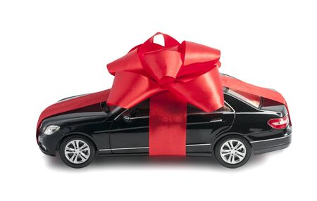 New black car with a red bow and ribbon isolated on a white background side view Stock Photo
