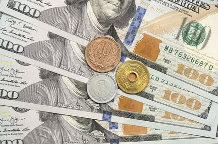 Japanese Yen coin on top of dollar bills for financial and investment concepts