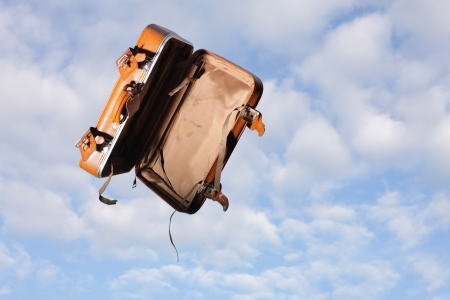 Empty suitcase flying through cloudy sky background  Stock Photo