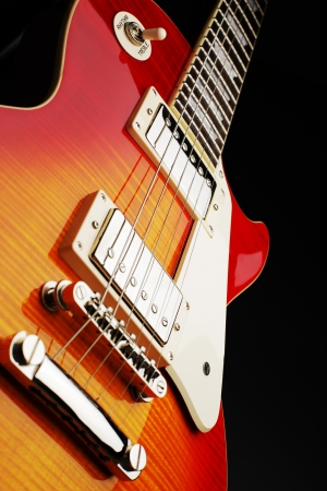 Closeup view of the bridge, strings,pickups and pickguard of a wooden electric guitar showing beautiful wood grain detail