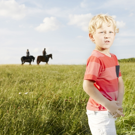 Young blonde boy standing in a grassy field with two horse riders silhouetted on the skyline in the background Stock Photo