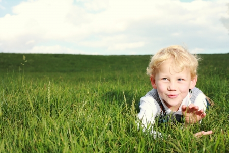 Happy little boy lying in an open green grassy field clapping his hands and showing appreciation with a mischievous smile