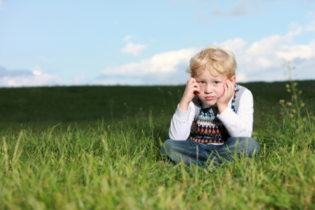glum: Glum little boy sitting in grass with his chin resting on his hands and a despondent expression