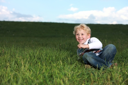 Cheerful small boy rolling around in the grass having a good laugh as he watches someone off camera