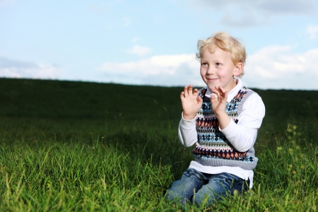 Impish little boy kneeling in a shaft of sunshine in green field smiling as he raises his hands to his chest