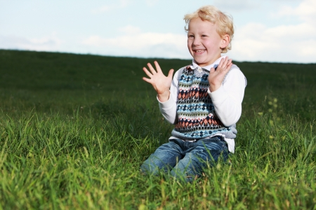 Little boy kneeling in a large grassy green field clapping his hands in glee