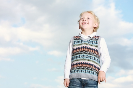 Low angle view of a spontaneous cheerful little boy grinning happily as he stands watching something in the distance