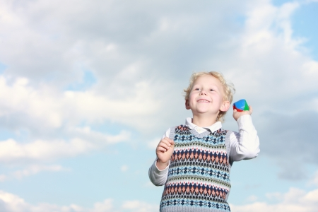 Low angle view against a cloudy sky of a happy little boy throwing a colourful ball with copyspace Stock Photo
