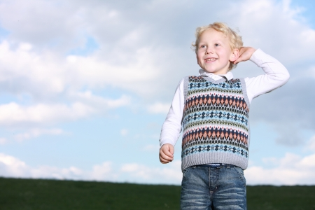 Low angle view against cloudy blue sky of a cheerful grinning little blonde boy standing in a green field with his hand raised to face
