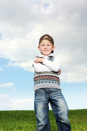 Smiling confident young boy standing with his arms folded over his chest and looking down at the camera with amusement