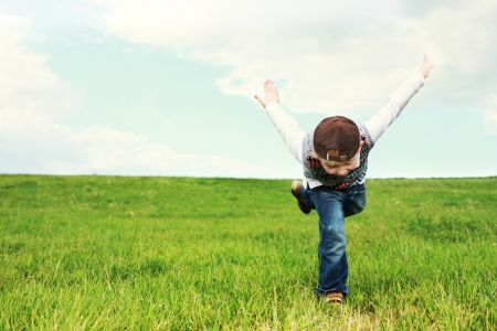 Young boy playing in a green grassy field pretending to be a bird or aeroplane as he balances on one leg with his arms raised