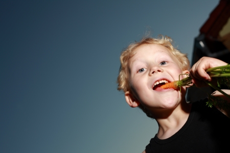 Low angle view of a young blonde boy munching a freshly pulled carrot which still has its leaves