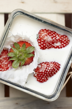 Large ripe red strawberry falling and splashing into milk containing three other floating strawberries Stock Photo