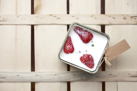 Overhead view of three ripe red strawberries floating in a square container filled with milk