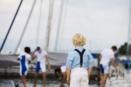 Little boy with curly blonde hair standing with his back to the camera watching his favourite sports team Stock Photo