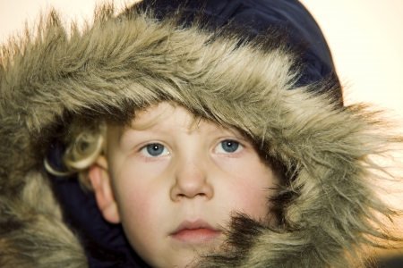 Serious little boy wearing a fur lined hood surrounding his face for warmth in winter
