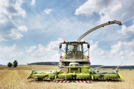 Modern agricultural combine harvester and thresher standing in a freshly harvested field photo