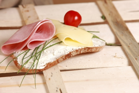 Open sandwich on a slice of rye bread with ham and cheese garnished with fresh chives and a cocktail tomato