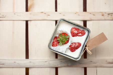 Overhead view of a ripe red strawberry being dropped into a container of milk with a splash Stock Photo