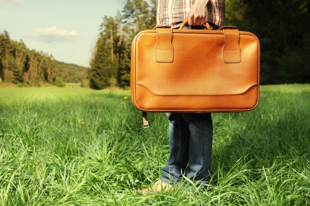Man with vintage travel bag standing on green lawn - travel concept Stock Photo