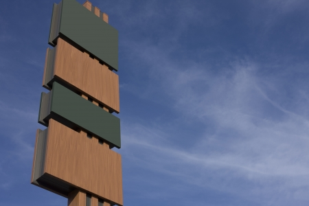 alternating: Tall blank signboard with alternating panels in green and brown with copyspace for your text ot information against a hazy blue sky Stock Photo