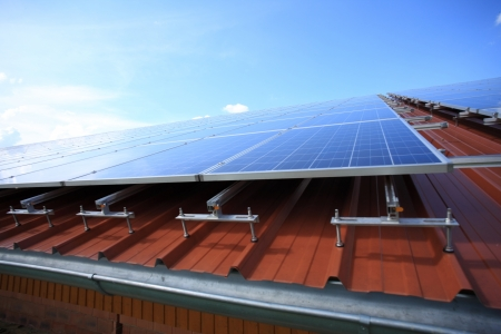 Solar panels placed on roof against blue sky Stock Photo