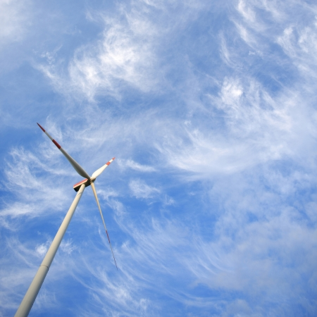 Windmill against blue sky with copy space - renewable energy concept