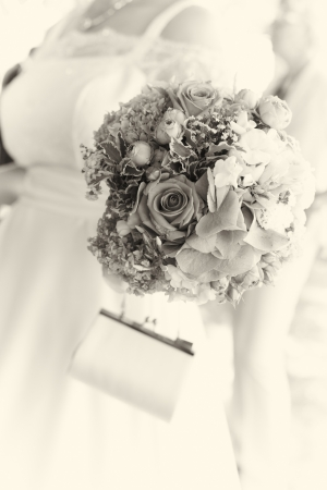 Artsiticall toned image of a bride carrying her bouquet with selective focus to the flowers