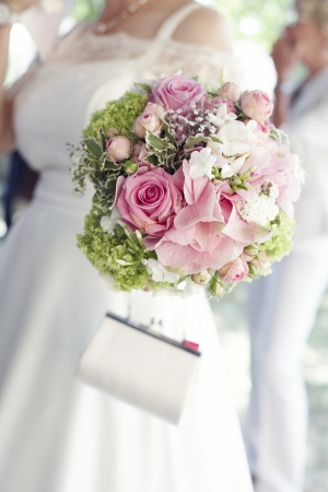 Selective focus on pretty pink roses in a circular bridal bouquet being carried by the bride in her bridal gown
