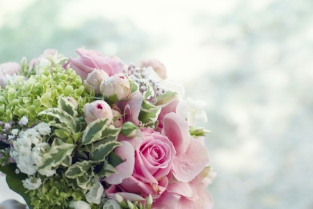 Closeup background of a bridal bouquet with lovely pink roses and variegated foliage outdoors with copyspace