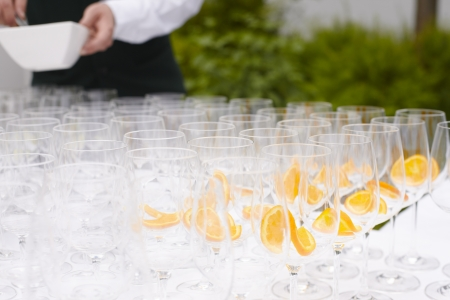 Rows of empty flutes and glasses being prepared with slices of orange before being filled with champagne for toasting and speeches