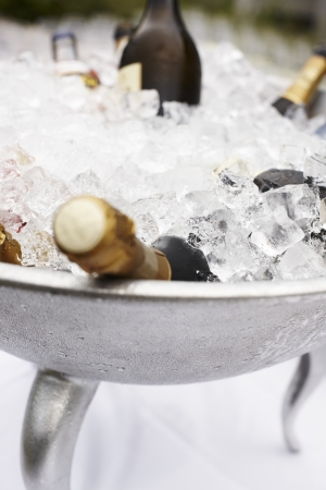 Multiple bottles of unopened champagne cooling in a large metal container of ice at a wedding or catered function Stock Photo