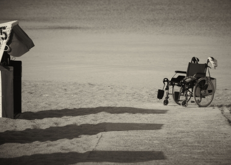Monochrome image of an abandoned empty wheelchair parked on the edge of sand as it was not able to be wheeled any further over the soft terrain