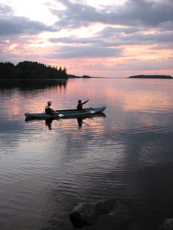 Two people in kayak on the sunset background