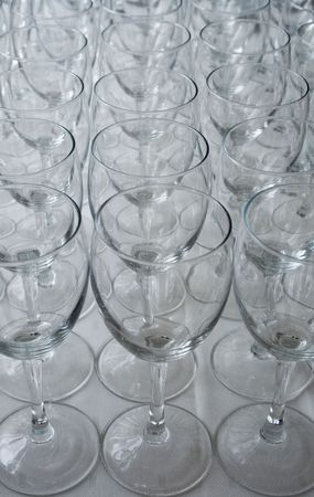 lines of empty wine glasses on cloth