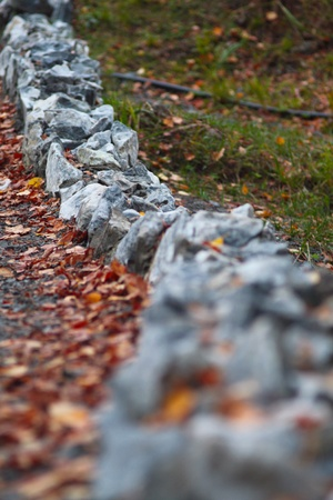 border of marble stones covered with leaves