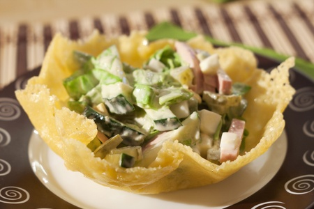 salad with mayonnaise sauce in a cheese basket Stock Photo
