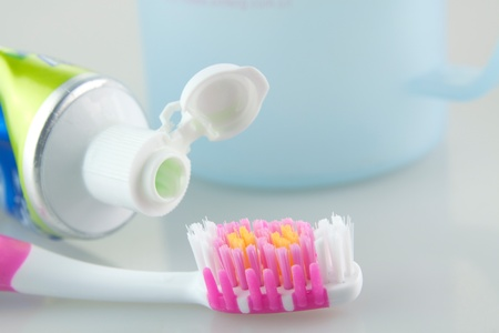toothpaste: Toothbrush and toothpaste are placed next to the Cup Stock Photo