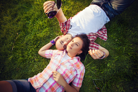 cheerful young couple relaxing in the park on the grass and in the city photo