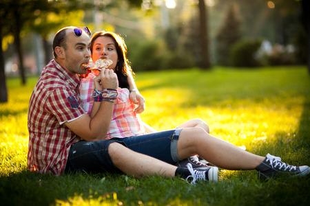 position d amour: gaie jeune couple de détente dans le parc sur l'herbe et dans la ville