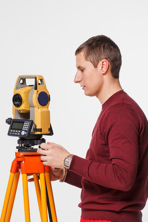 geodesist: Worker looking into the level white isolated