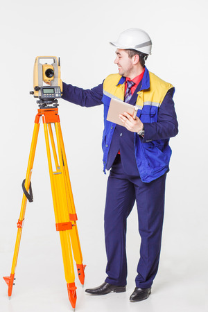 geodesy: Worker looking into the level white isolated