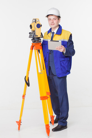 surveyors: Worker looking into the level white isolated
